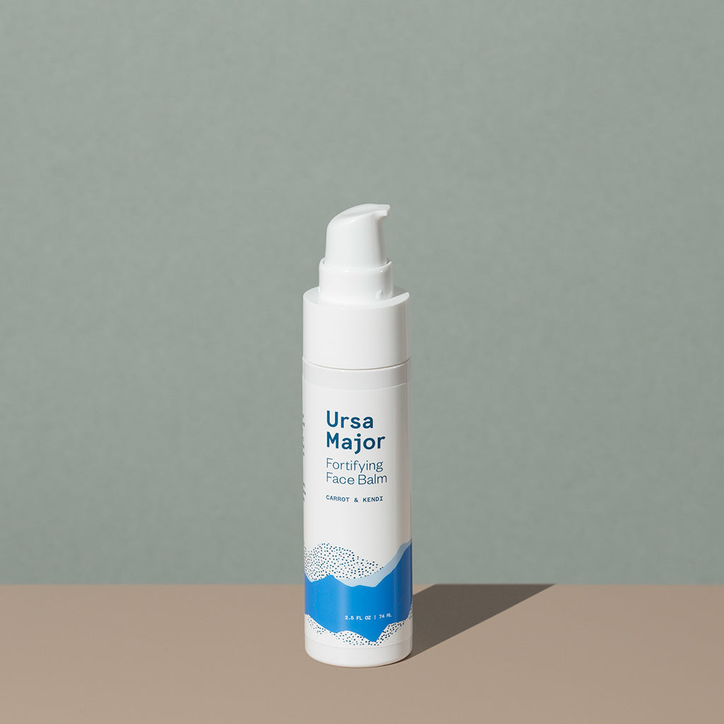 Ursa Major Fortifying Face Balm in a small white cylindric plastic bottle with a press down dispenser cap and a blue labeling of mountains