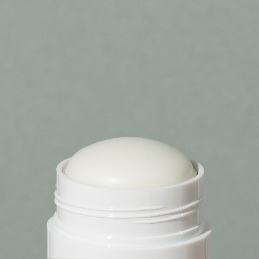Close up details of white wax creamy Ursa Major base layer deodorant in a white small cylindric plastic container with a cap and green labeling of mountains