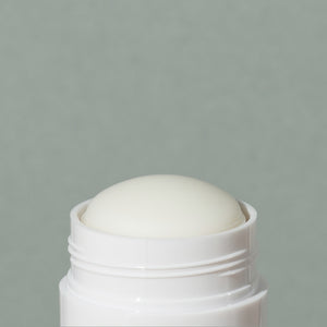 Close up details of wax creamy Ursa Major Hoppin' Fresh natural deodorant in a white small cylindric plastic container with a cap and green labeling of mountains