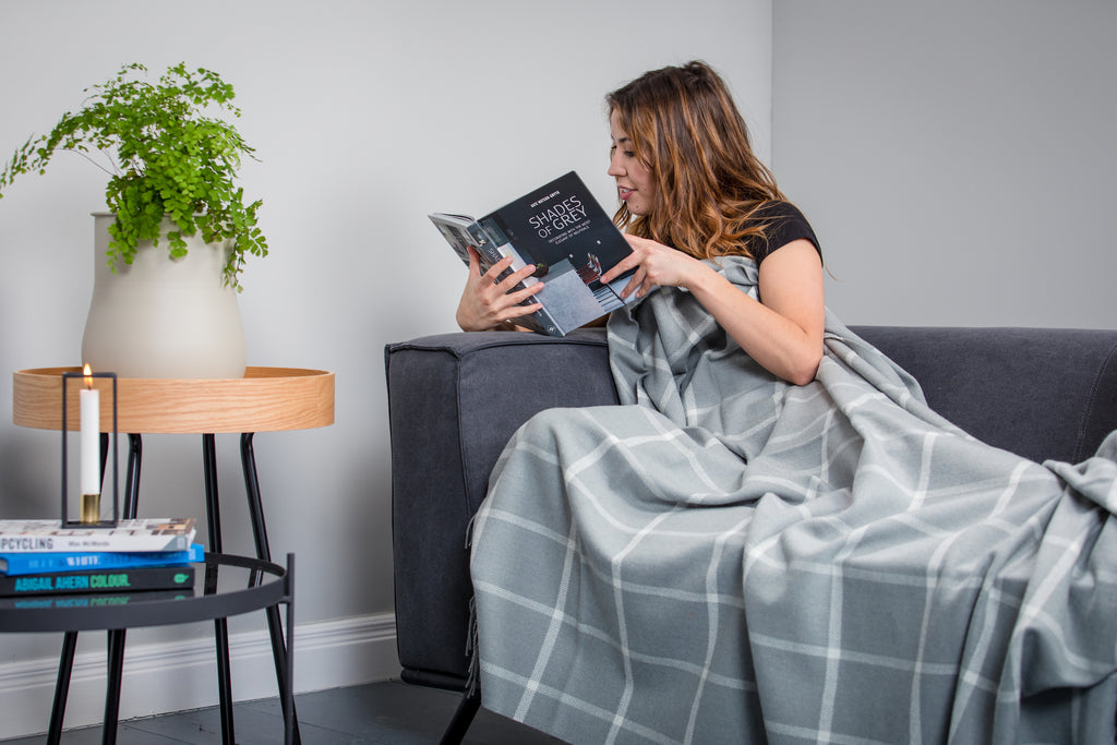Woman wrapped up in Foxford's Aqua Windowpane Throw reading a book