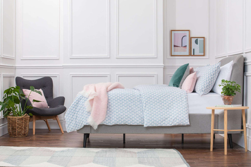 Bedroom shot of Aqua and Pale Pink Geometric Patterned Duvet Cover with a wooden side table next to the bed with a plant on top and a grey chair at the end of the bed with a pink cushion on. Made from 100% pure cotton in 300 thread count. Foxford Woollen Mills