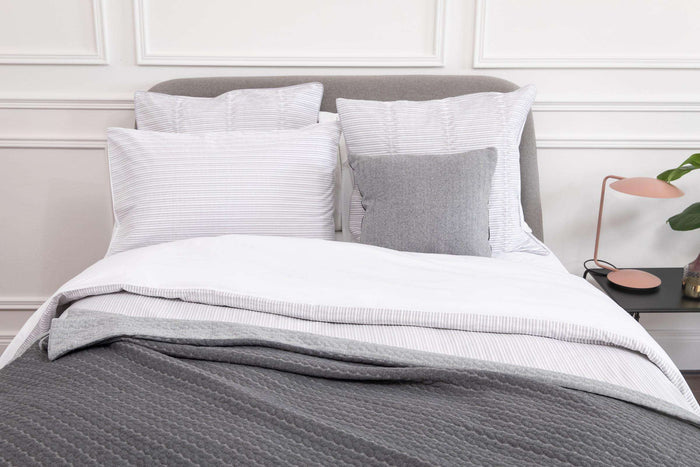 Bedroom shot of Foxford's Silver Pleats Pillowcases. Presented on a bed accessorised with grey cushions and throws. 100% Portuguese Cotton. By Foxford
