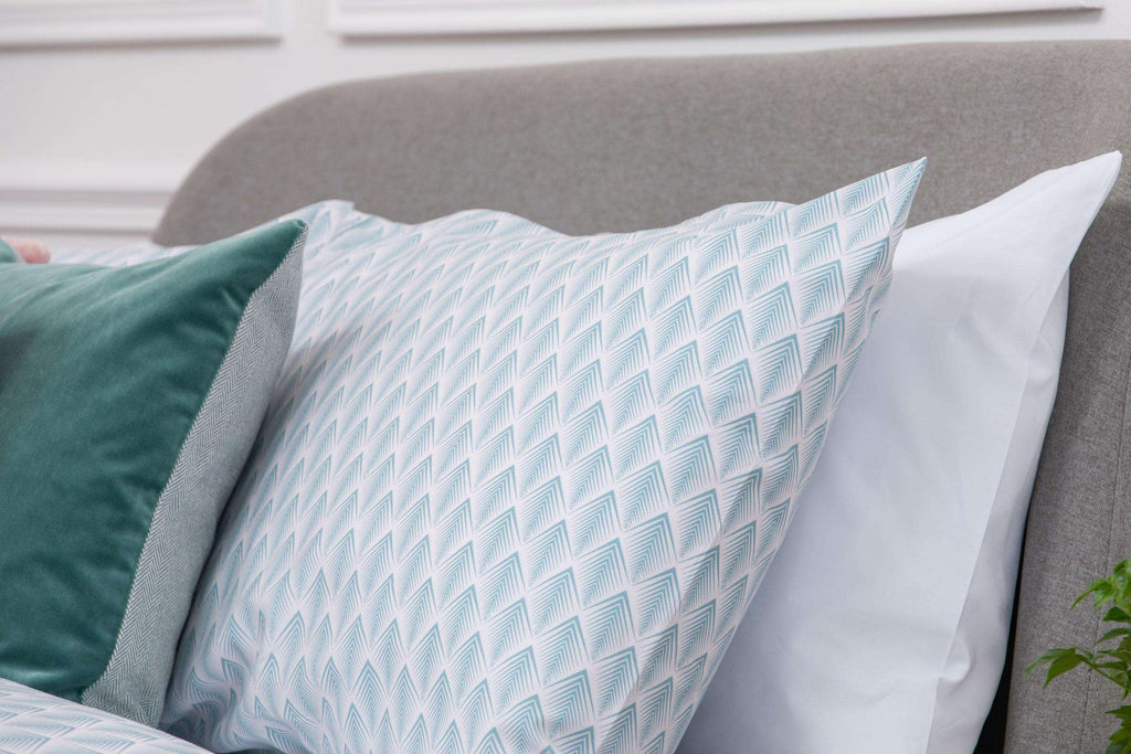 Bedroom shot of Aqua and Pale Pink Geometric Patterned pillow case placed on bed with a blue cushion on top. Made from 100% pure cotton in 300 thread count. Foxford Woollen Mills