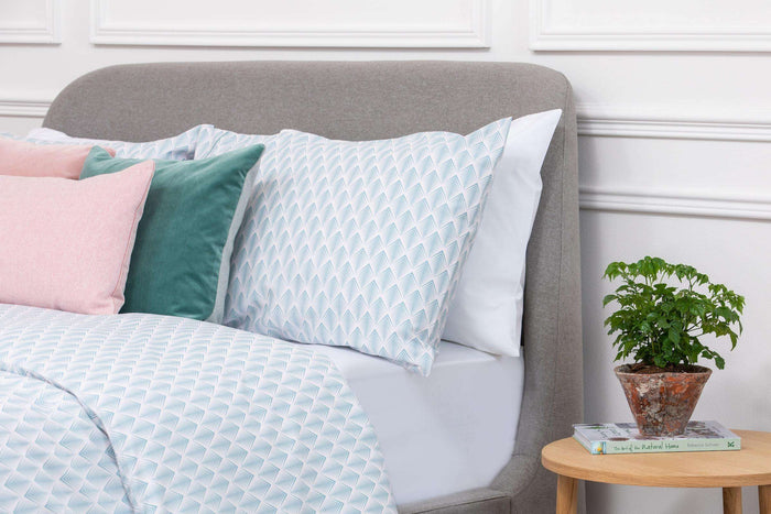 Bedroom shot of Aqua and Pale Pink Geometric Patterned pillow case placed on bed with pink and blue cushions on top. Made from 100% pure cotton in 300 thread count. Foxford Woollen Mills