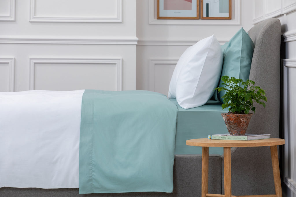 Bedroom shot of Aqua Sateen Bed Linen Set with wooden side table next to the bed with a plant on top. Made from 100% pure cotton in 300 thread count. Foxford Woollen Mills