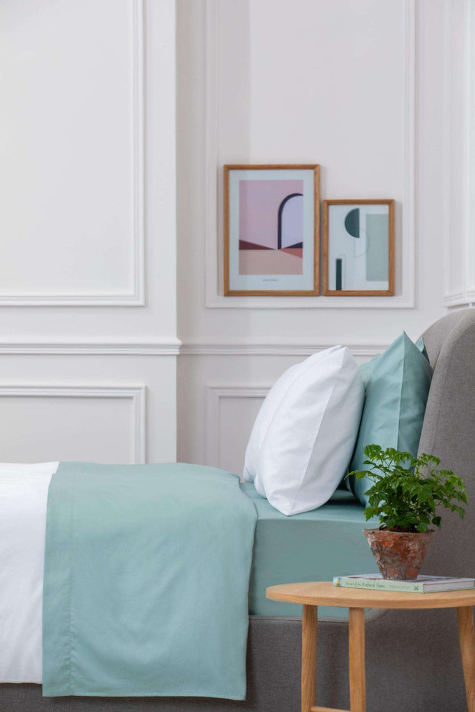 Bedroom shot of Aqua Sateen Flat Sheet with a wooden bedside table next to the bed with a plant on top. Made from 100% pure cotton in 300 thread count. Foxford Woollen Mills