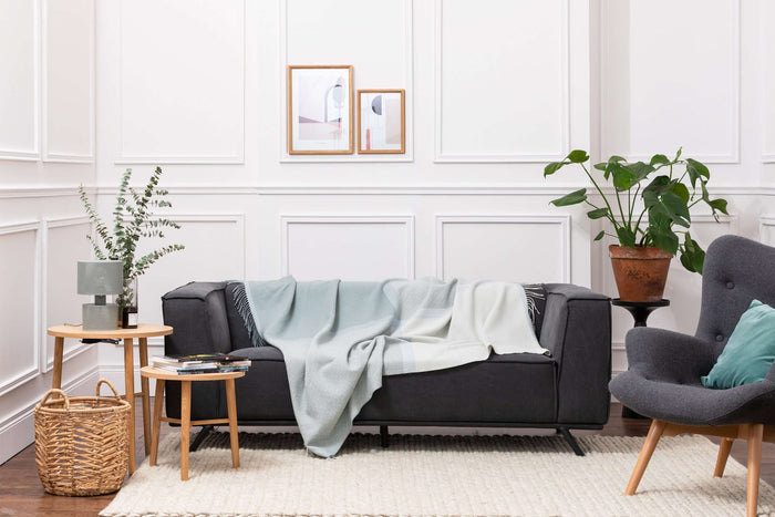 Giant Colour Block Aqua Lambswool Throw Draped Across Grey Couch