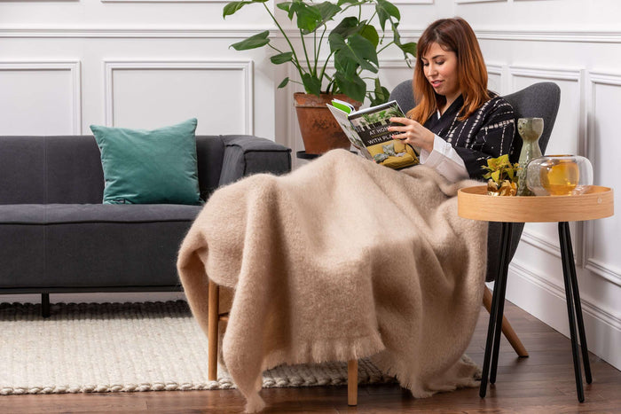 Woman relaxing on Grey Angel Chair wrapped in Foxford's Solid Bone Mohair Throw
