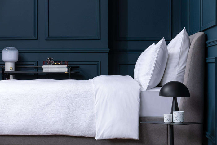 Bedroom shot of Foxford's Seersucker Duvet Cover. Presented on a bed against Navy walls. By Foxford Woollen Mills