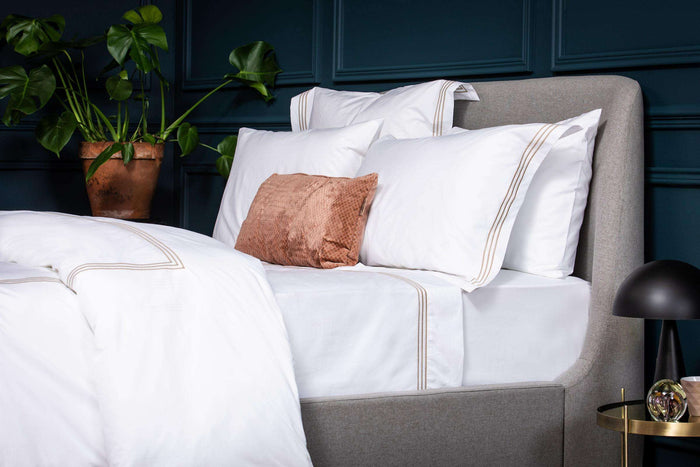 Product shot of Bone 3 Row Embroidered Egyptian Cotton Duvet Cover. Presented on bed with bone cushions and navy walls. Foxford Woollen Mills