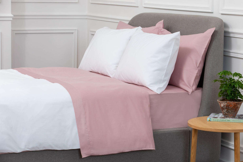 Bedroom shot of Foxford's Pink Sateen Fitted Sheet. Presented on a bed & accessories with pink & white pillows. 100% Portuguese Cotton. By Foxford