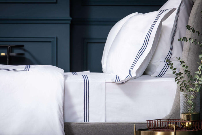 Bedroom shot of Foxford's Navy 3 Row Embroidered Egyptian Cotton Duvet Cover. Presented on a Bed against Navy Walls
