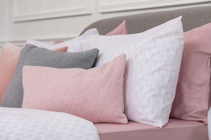 Bedroom shot of Foxford's Pink and White Geometric Housewife Pillowcase accessories with Pink and Grey Velvet Cushions. 100% Portuguese Cotton. By Foxford