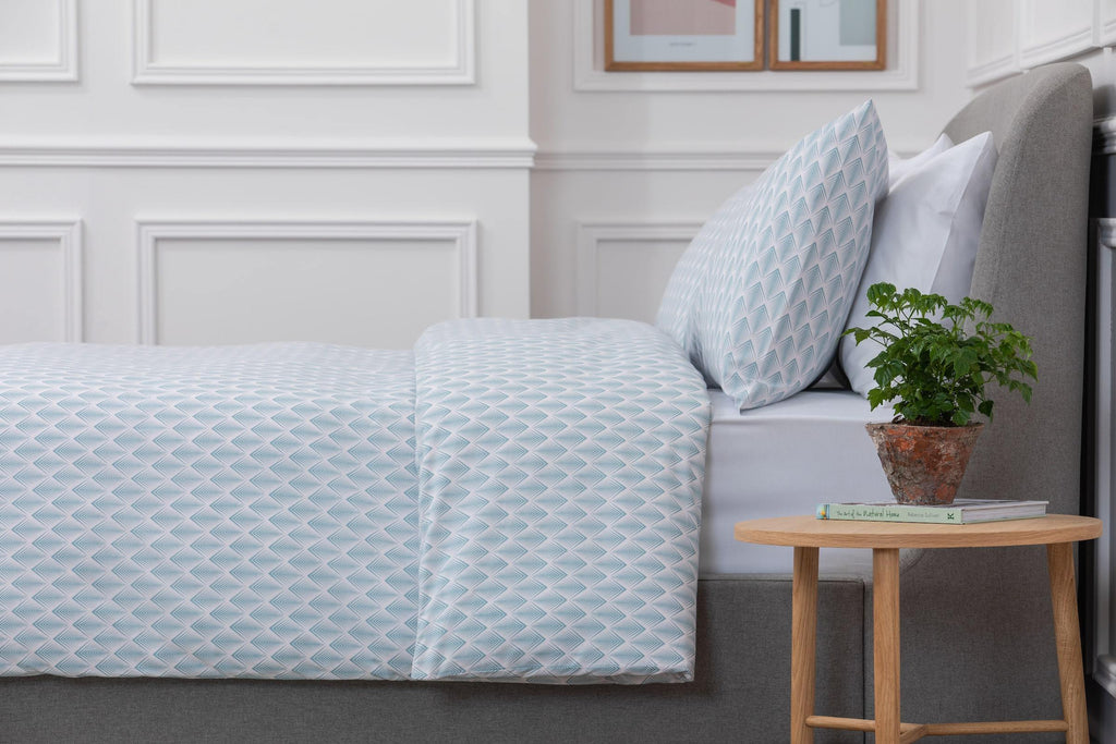 Bedroom shot of Aqua and Pale Pink Geometric Patterned Bed Linen Set with a wooden side table next to the bed with a plant on. Made from 100% pure cotton in 300 thread count. Foxford Woollen Mills