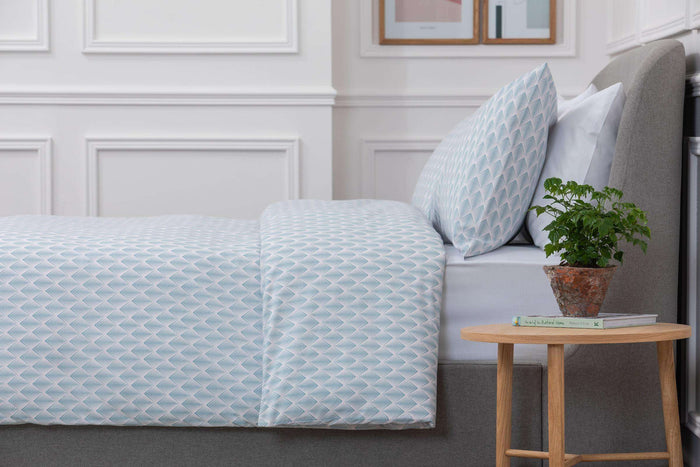 Bedroom shot of Aqua and Pale Pink Geometric Patterned Duvet Cover with a wooden side table next to the bed with a plant on top. Made from 100% pure cotton in 300 thread count. Foxford Woollen Mills