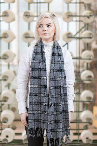 Woman wearing Foxford's Black Check Scarf in front of Woollen Mill Machine