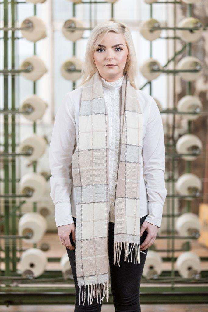 Woman wearing Foxford's Blush Block Check Scarf in Woollen Mill