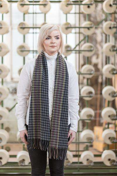 Woman wearing Foxford's Deep Grey Houndstooth Scarf in Woollen Mill