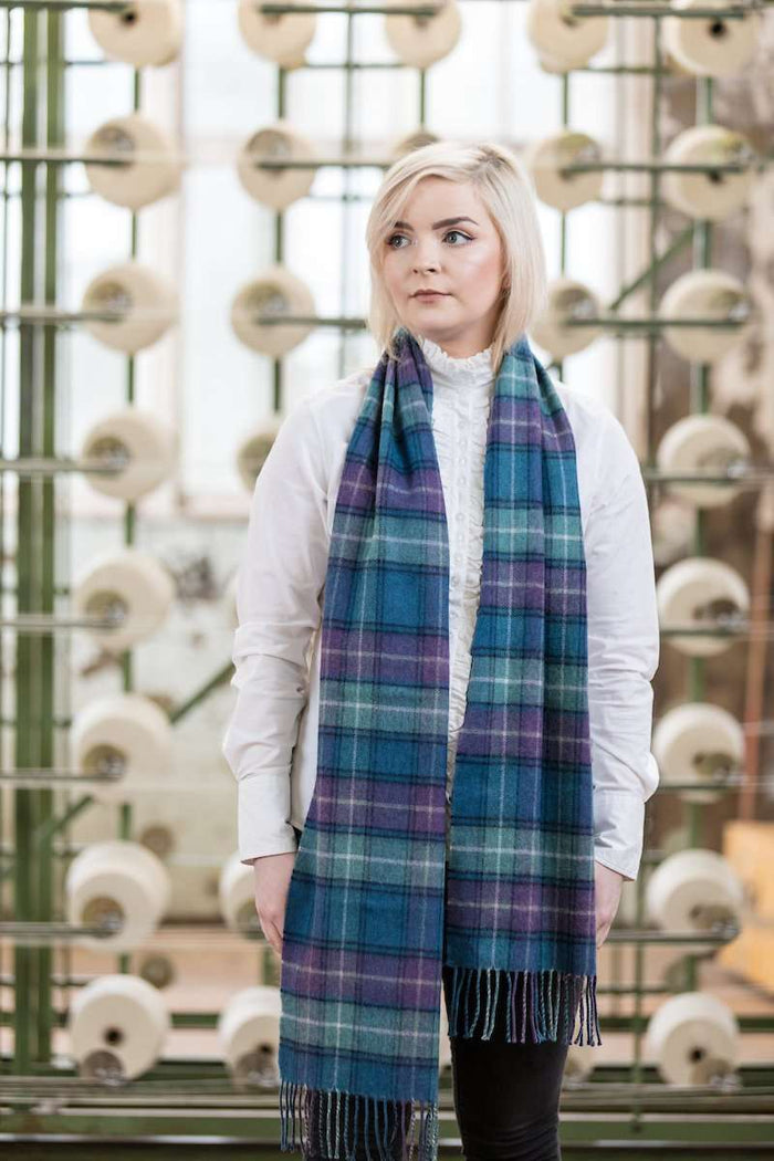 Woman wearing Foxford's Blue, Sage & Purple Scarf in Woollen Mill