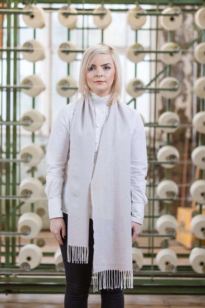 Woman wearing Foxford's Bone & White Scarf in Woollen Mill
