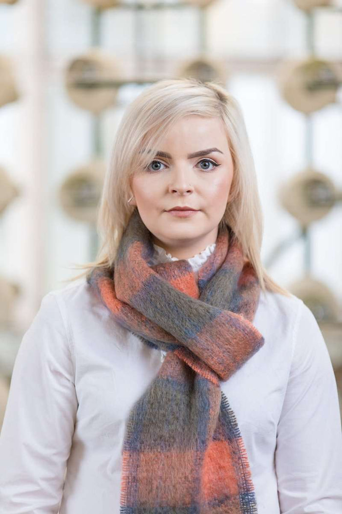 Woman wearing Foxford's Hague Blue & Burnt Orange Mohair Scarf