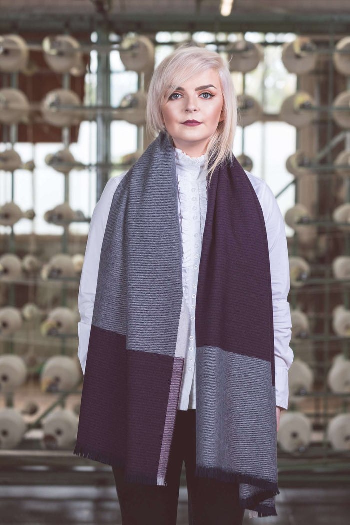 Woman standing in Mill wearing Foxford's Aubergine, Navy and Bone Stole