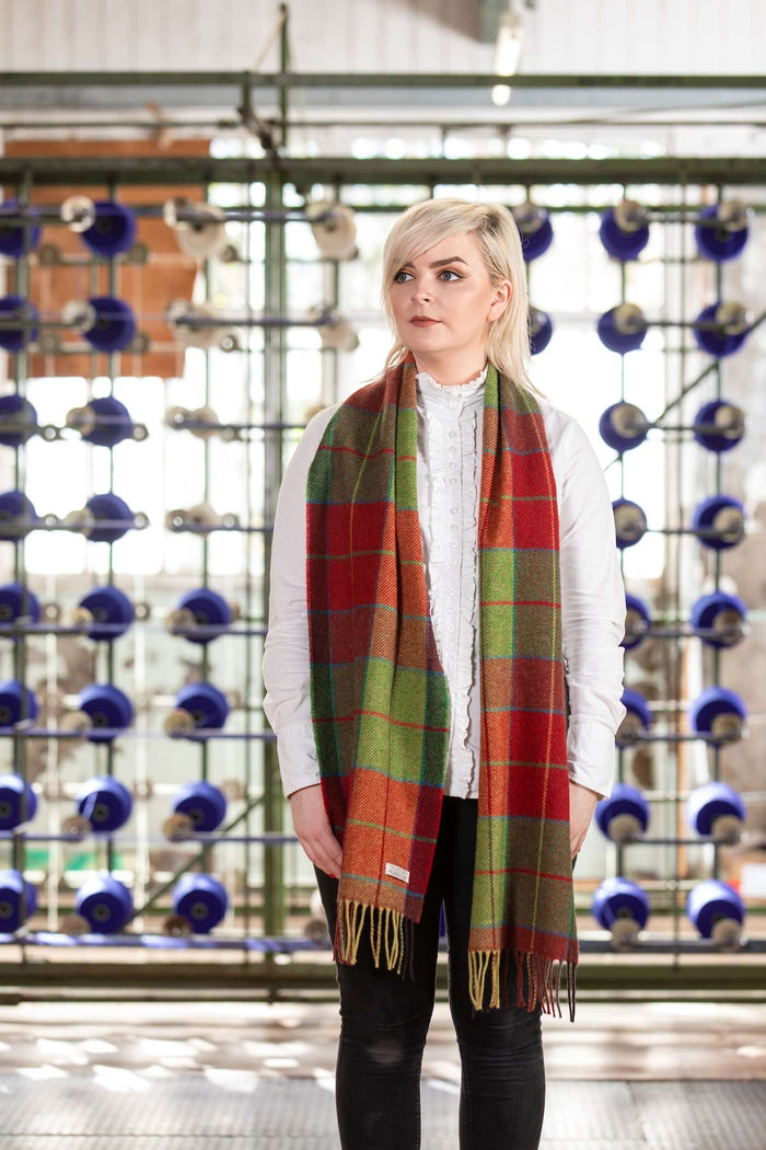 Woman wearing Foxford's Traditional Green and Red Block Check Scarf in Woollen Mill