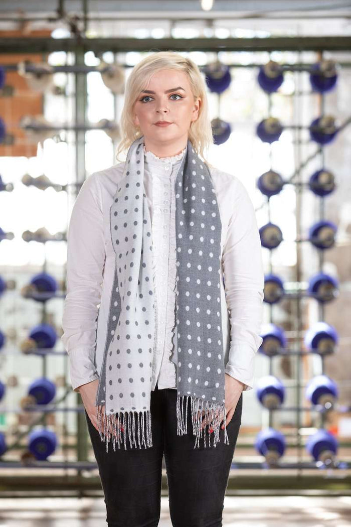 Woman wearing Foxford's Grey, White Spot Scarf in Woollen Mill