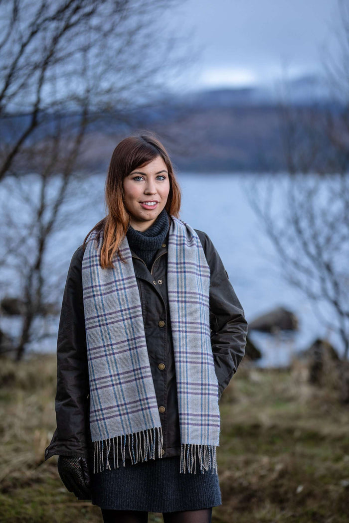 Woman wearing Foxford's Blue and Purple Glen Check Scarf in Irish Countryside