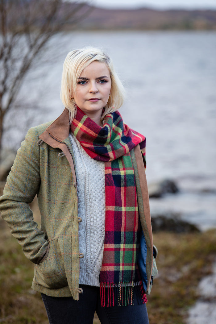 Woman wearing Foxford's Tomato Mirror Block Check Scarf beside River Moy