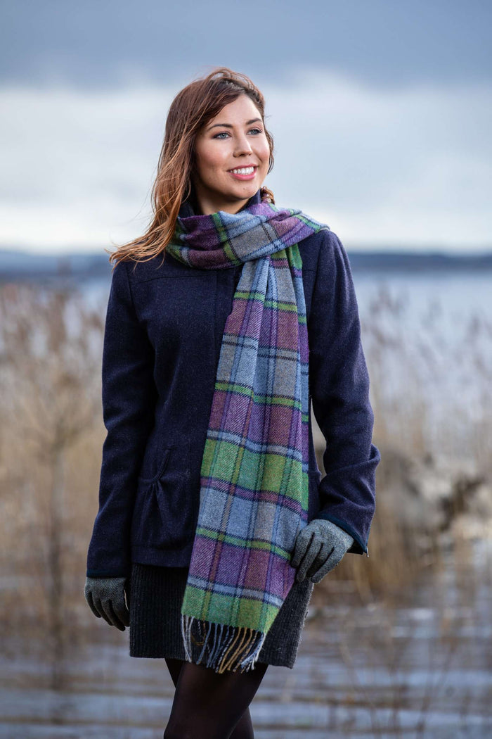 Woman wearing Foxford's Purple Heritage Block Windowpane Scarf beside Lough Conn