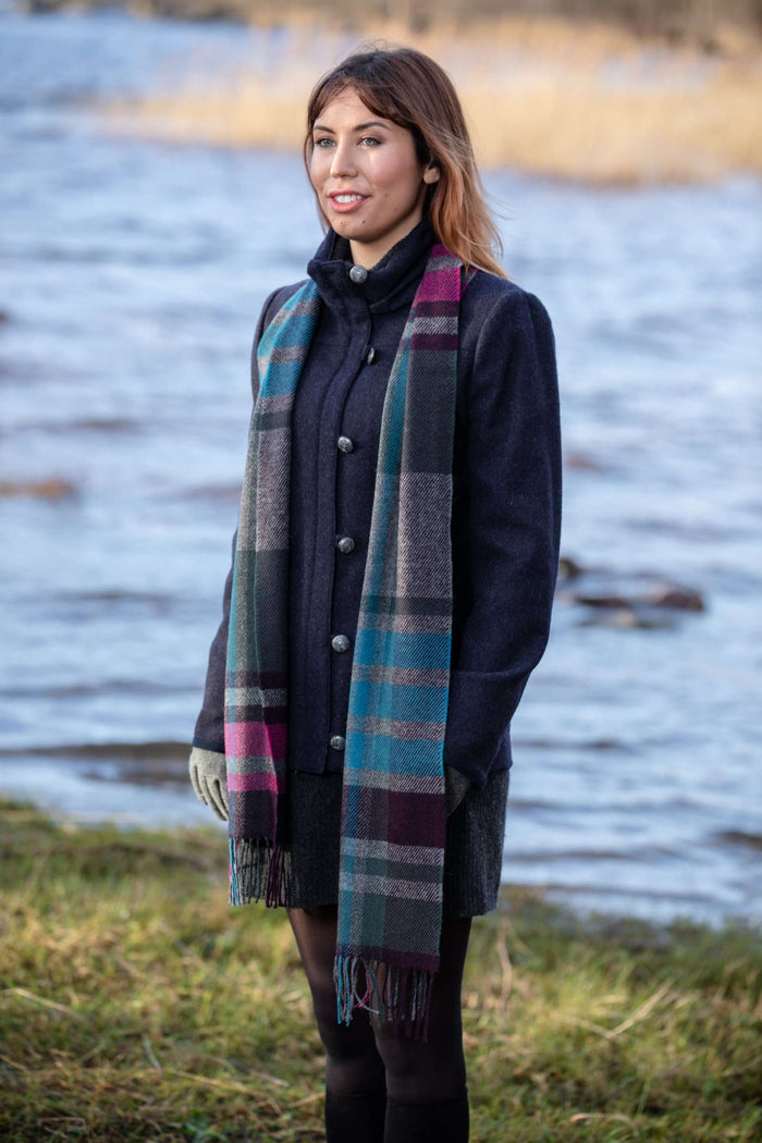 Woman wearing Foxford's Darks Warp Weft Stripe Scarf beside River Moy