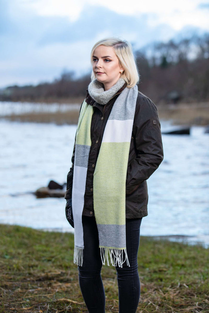 Woman wearing Foxford's White, Uniform and Citrus Stripe Scarf beside the River Moy