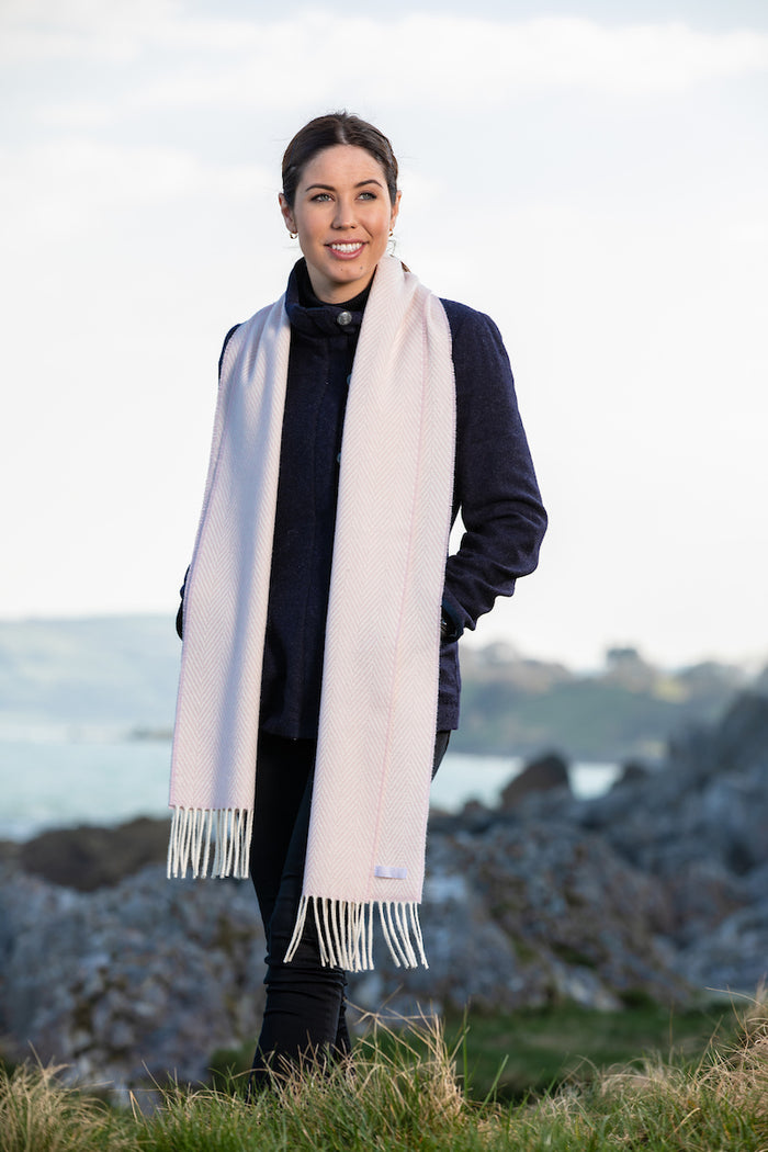 Woman wearing Foxford's Pink and White Herringbone Cashmere Scarf in Irish Countryside