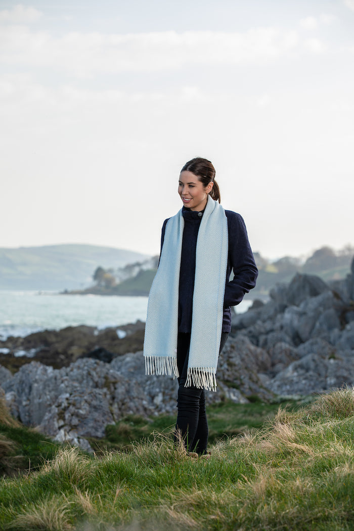 Woman wearing Foxford's Blue and White Herringbone Cashmere Scarf in Irish Countryside