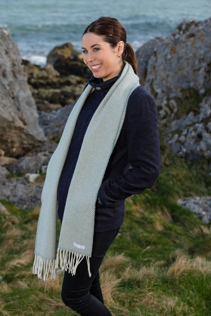 Woman wearing Foxford's Sage and White Herringbone Cashmere Scarf in the Irish Countryside