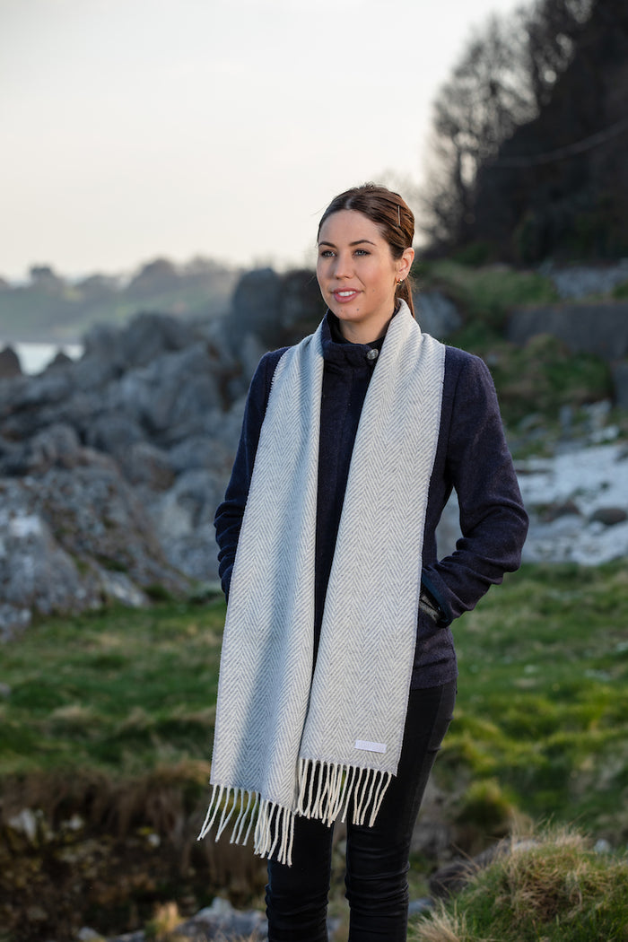 Woman wearing Foxford's Pearl Grey and White Herringbone Cashmere Scarf in Irish Countryside