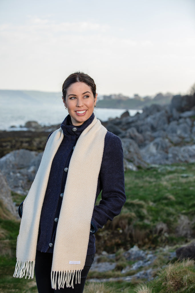 Woman smiling wearing Foxford's Bone and White Herringbone Cashmere Scarf in Irish Countryside