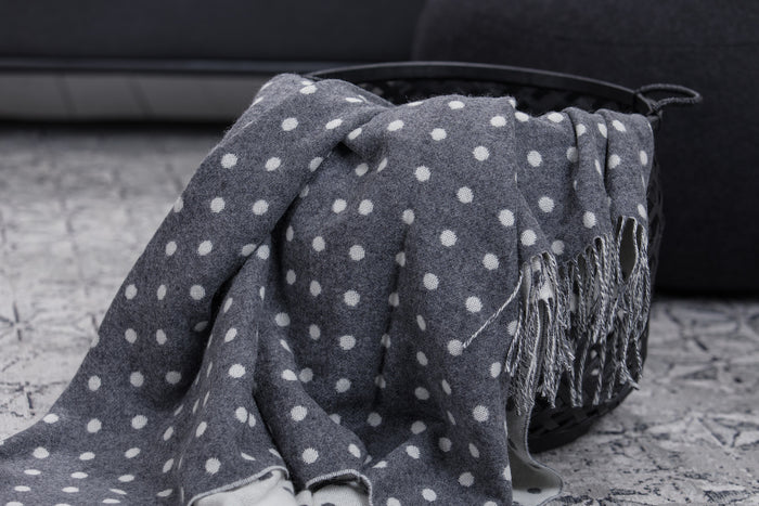 Grey & White Spot Lambswool Throw Draped out of Black Basket