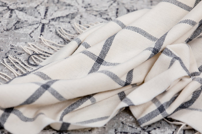 Foxford's White & Grey Windowpane Throw Draped Across Grey and Beige Carpet