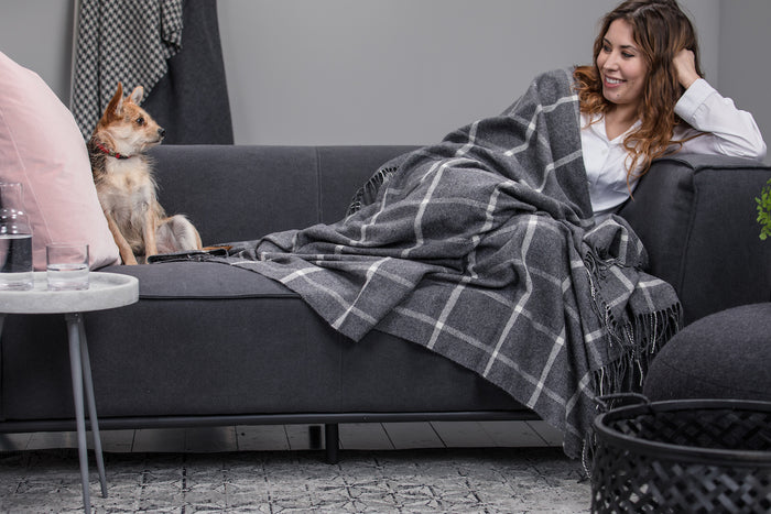 Woman & Dog cosy on grey couch with Grey Windowpane Throw