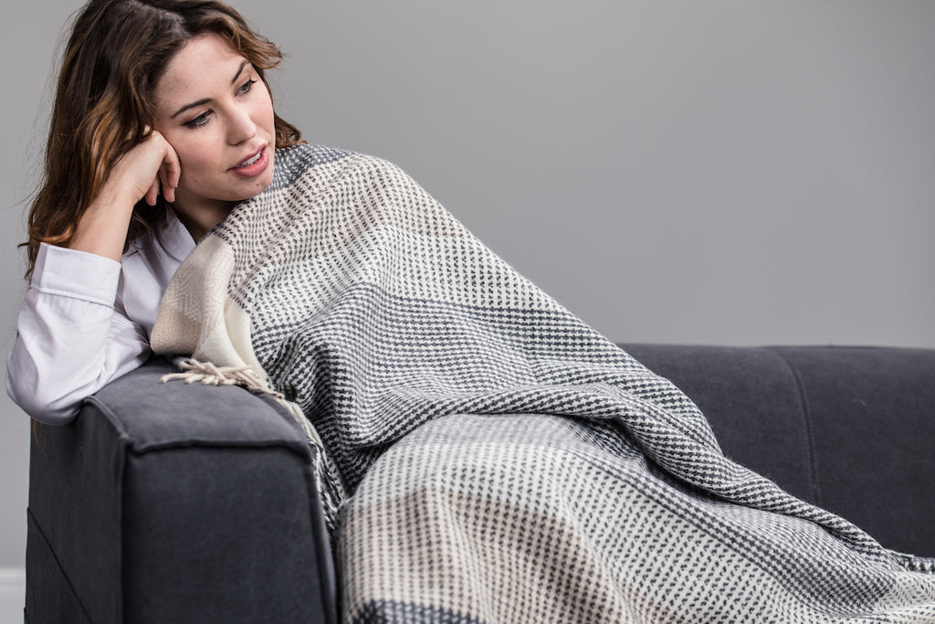 Woman wrapped up in Foxford's Grey, Bone & White Large Block Throw