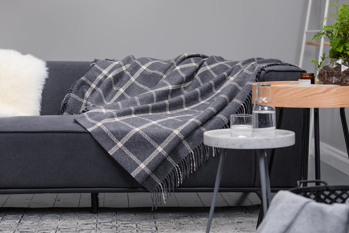 Grey & Bone Windowpane Cashmere Throw draped across a Grey Couch