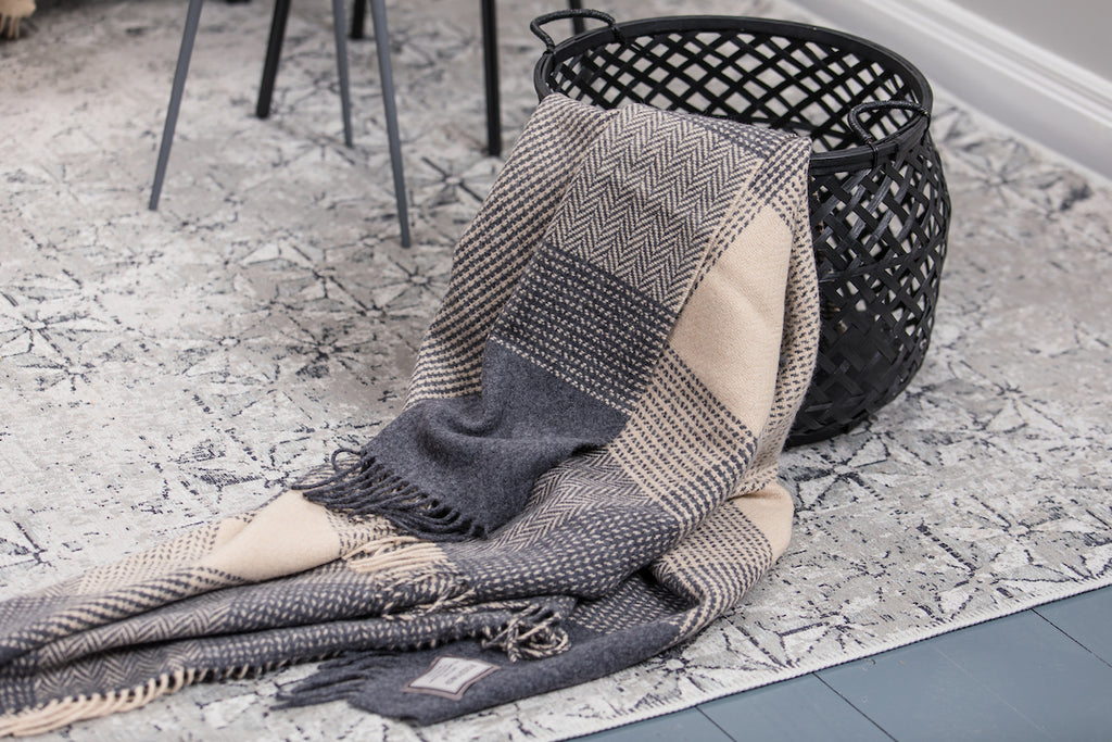 Oxford & Bone Large Block Cashmere Throw draped in Black Basket on Neutral Carpet