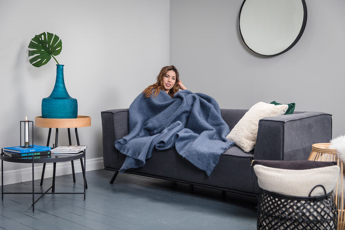 Woman wrapped up in Foxford's Hague Blue Mohair Throw on Grey Couch