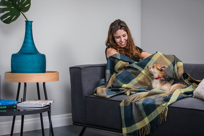 Women sitting on sofa with Foxford's Peacock Small Check Throw and small dog
