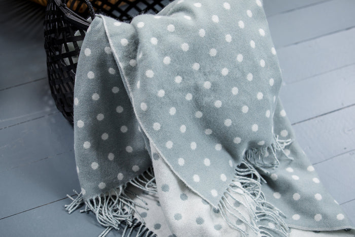 Aqua Spot Lambswool Throw Draped out of a Black Basket
