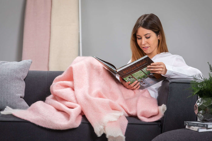 Woman curled up reading on grey couch wrapped in Foxford's Pink Mohair Throw