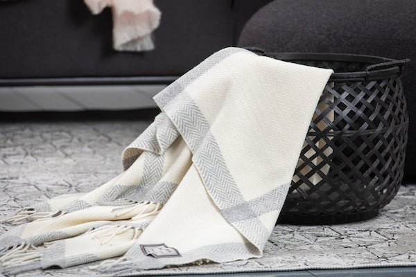Pearl Grey and White Windowpane Cashmere Throw Draped In Black Basket On a Neutral Carpet