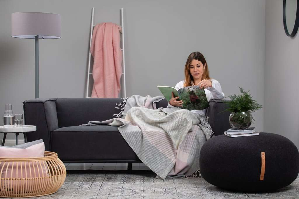 Woman wrapped in Foxford's Pearl Grey, Pink and White Cashmere Throw reading a book on a grey couch